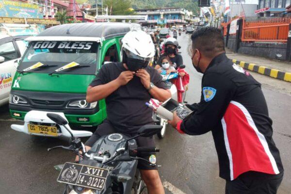 Anggota Komunitas Mobil MOC Jayapura membagikan masker kepada pengguna jalan dan pengunjung maupun pedagang Pasar Youtefa Kotaraja, Kelurahan Way Mhorock, Distrik Abepura, Kota Jayapura.