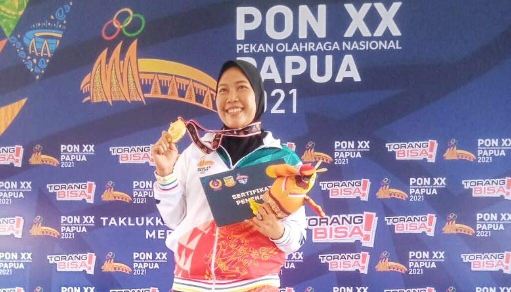 Atlet Menembak Putri Papua, Nourma Try Indriani ketika memamerkan medali emas yang diperolehnya di nomor 10 meter running target women individu. 9Foto : Irfan)