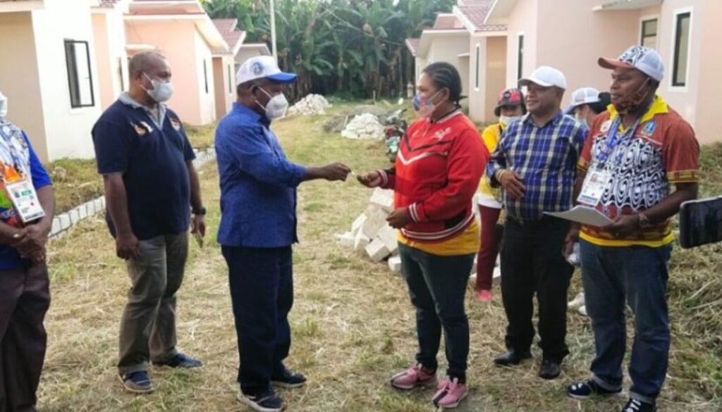 Penyerahan kunci rumah oleh Bupati Kabupaten Jayapura Mathius Awoitauw kepada Mantan Atlet dayung berprestasi, Erni Sokoy.(Foto : Humas PB PON XX Papua)